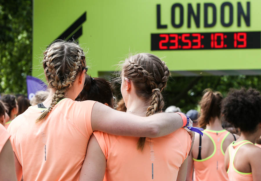 Reportage photograph of women embracing prior to the Nike run event in Victoria Park, East London