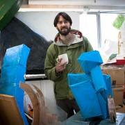 Environmental portrait of artist John Wallbank in his sculpture studio in Stratford, London