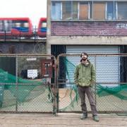 Environmental portrait of artist John Wallbank outside his sculpture studio in Stratford, London