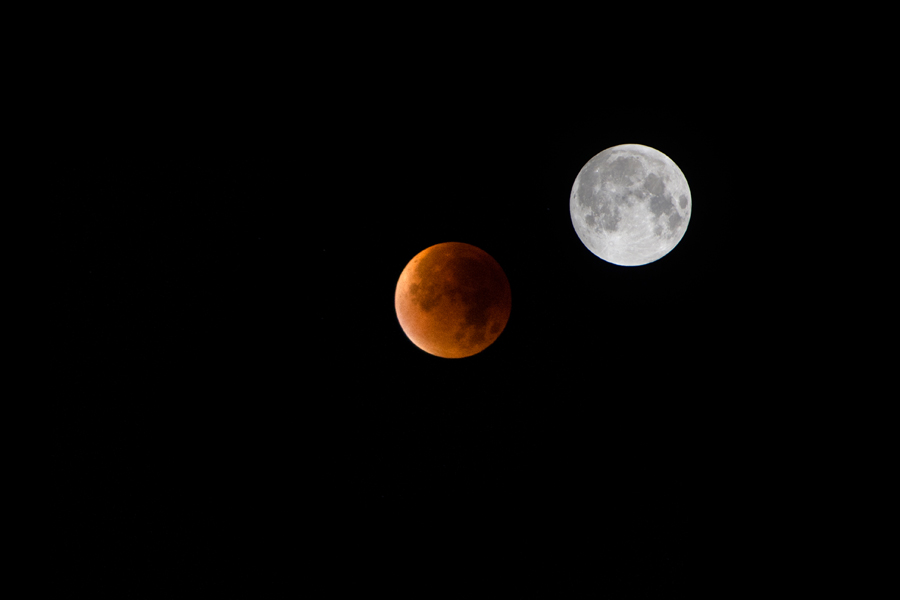 Superimposed images of blood moon total lunar eclipse and an earlier un-eclipsed super moon that night