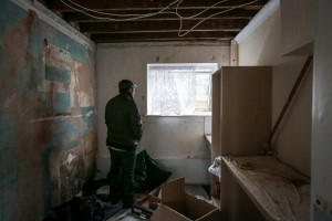 An asylum seeker looks from a window of a disused room at